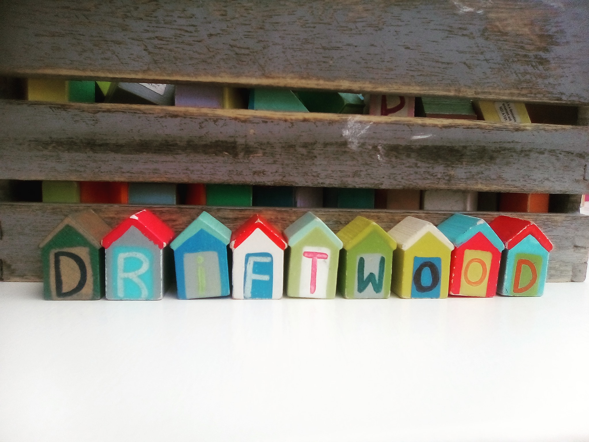 A row of colourful mini beach huts stands in front of a wooden background. Each huts spells out one letter of the word Driftwood,