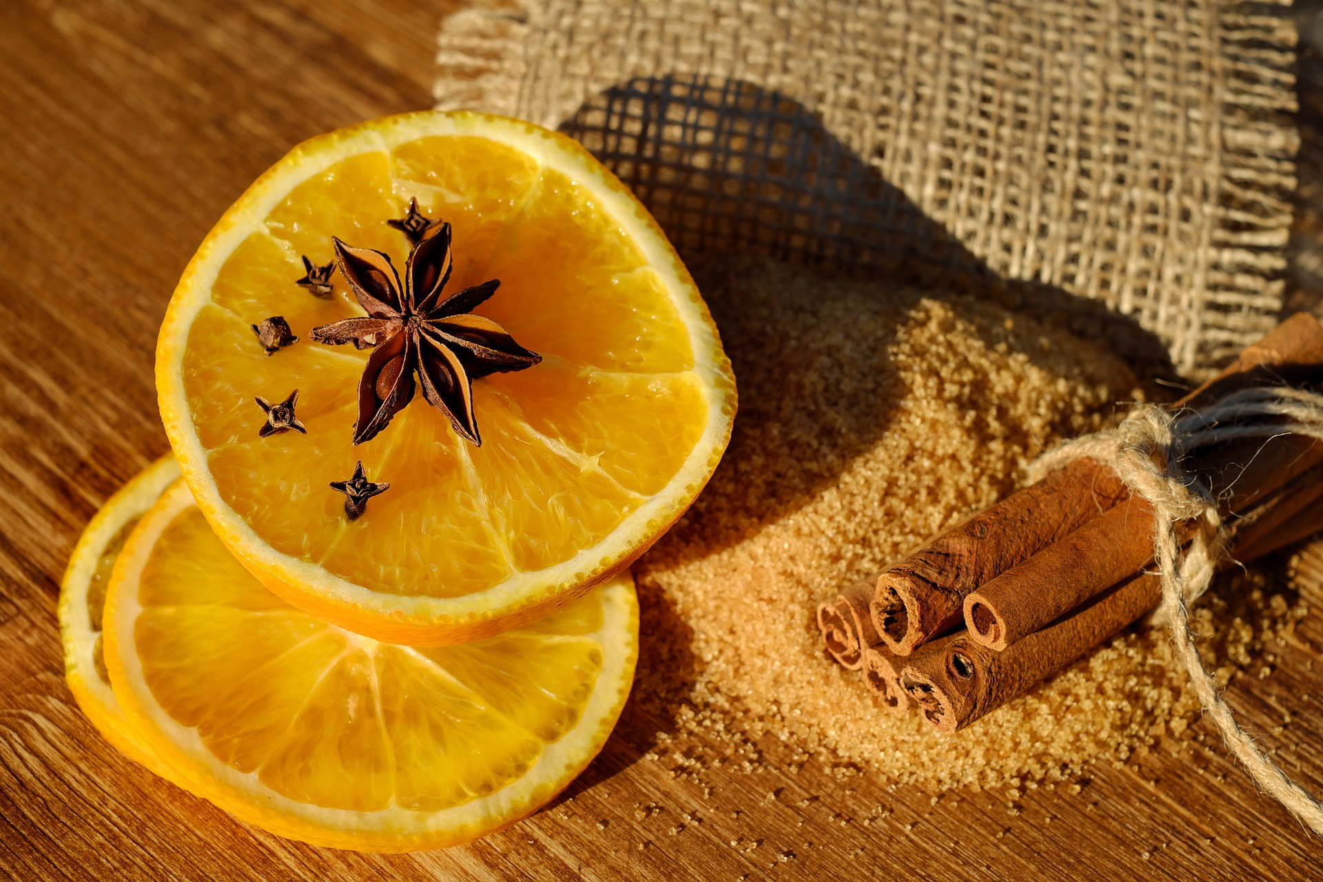 Slices of orange lie on a wooden surface, with star anise on top and a bundle of cinnamon to the right,