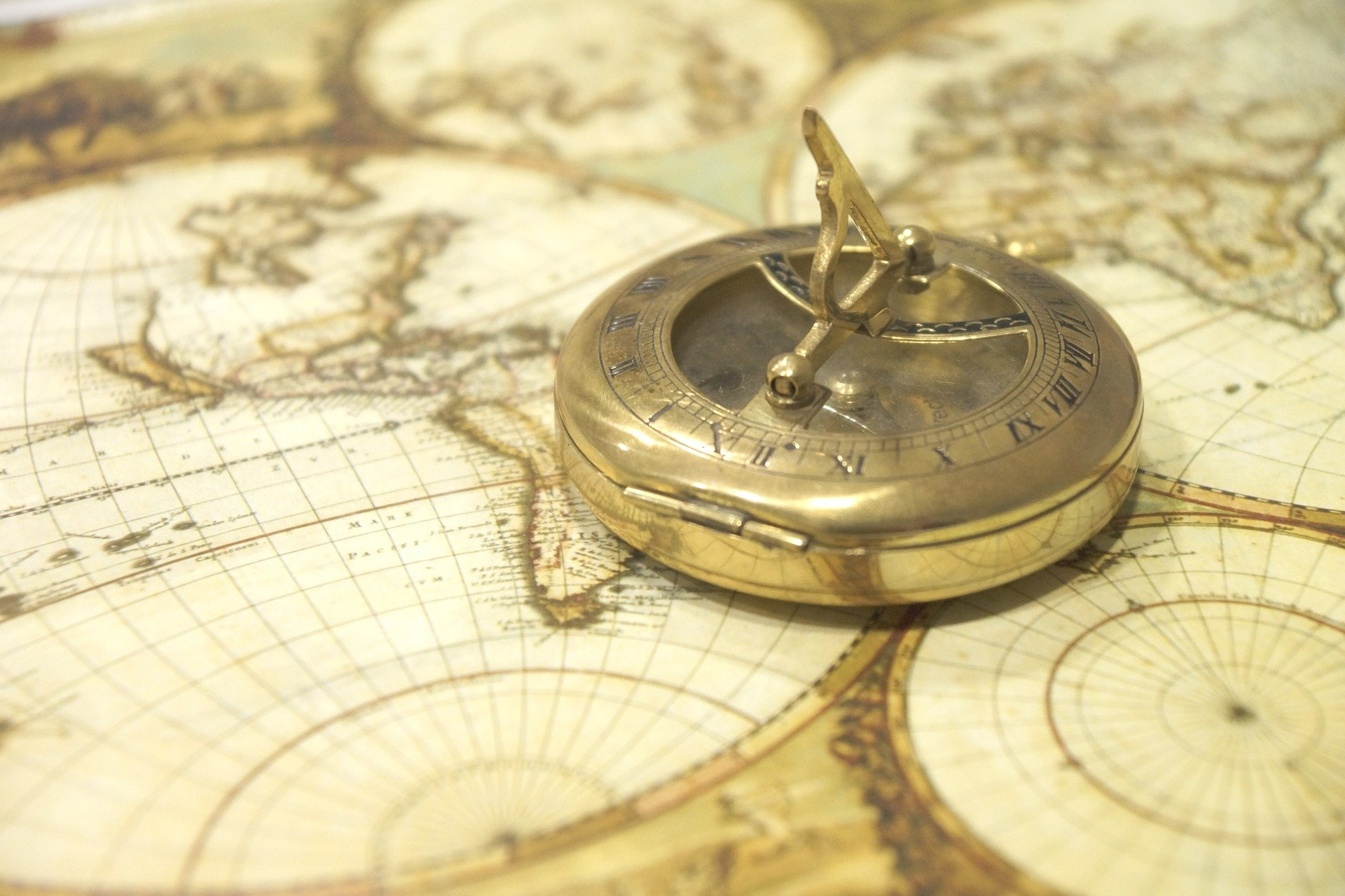 An old-fashioned compass and sun dial lies on top of an old map.