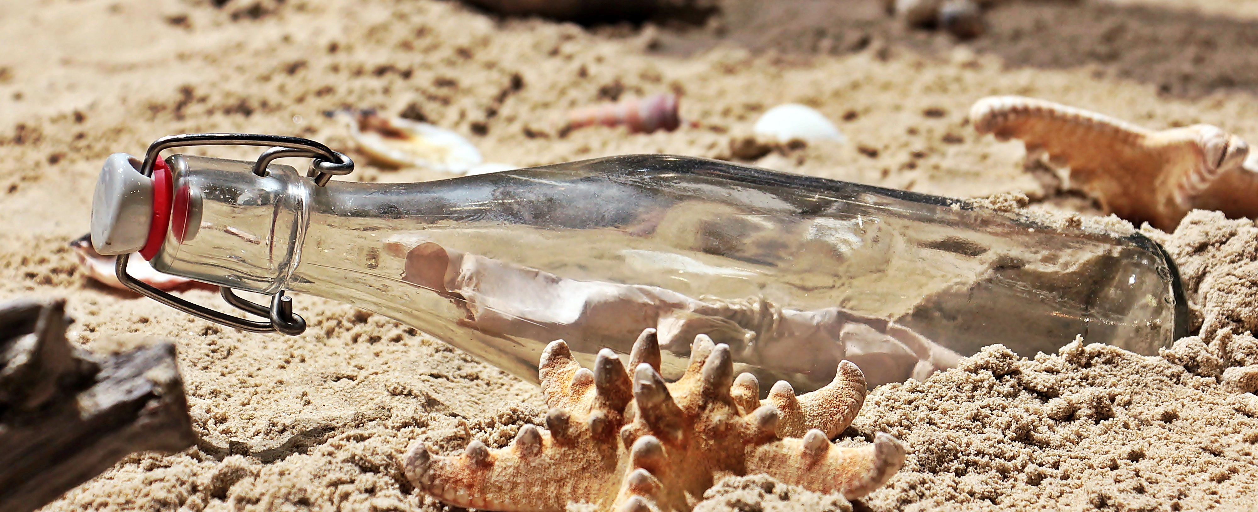 A bottle lies on its side in the sand. Inside is a rolled up message on aged paper.